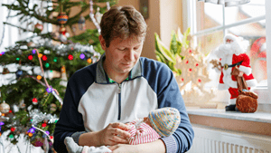New dad holds baby during Christmas at the hospital